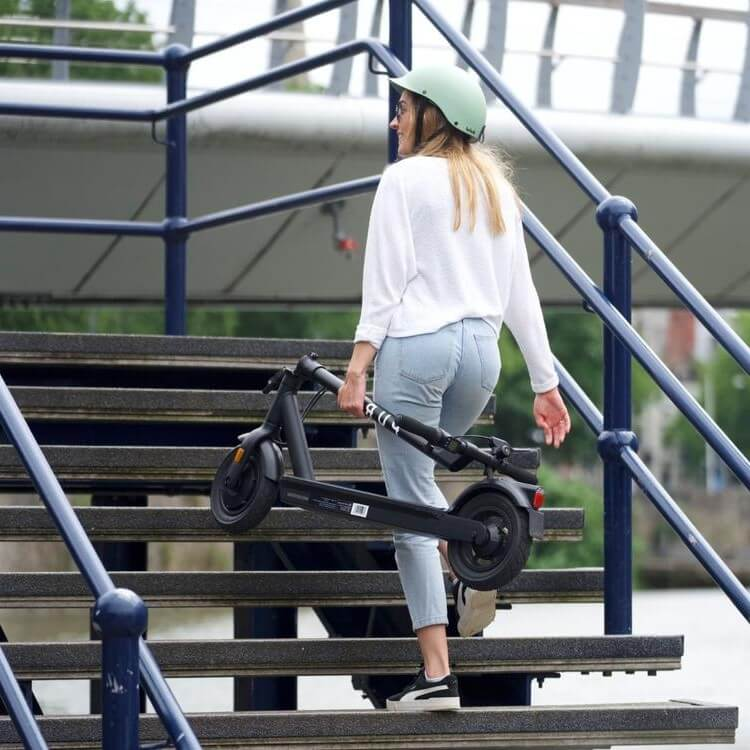 woman carrying the e-scooter up a flight of stairs