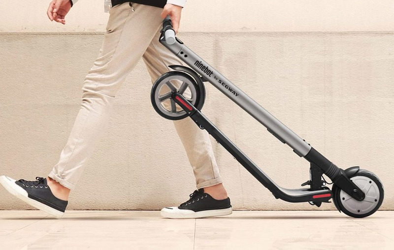 Man wheeling the ES2 electric scooter in its folded position