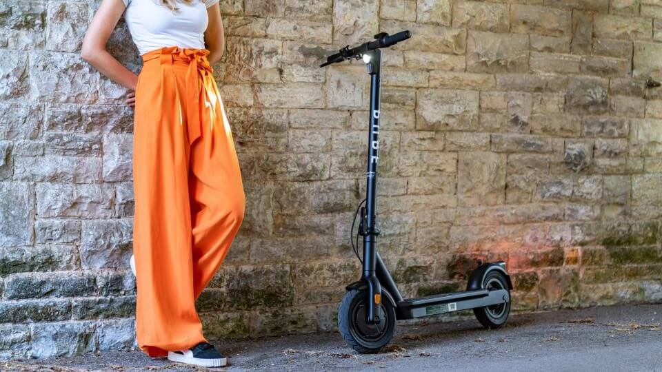 Attractive woman stood next to her Pure Air Pro electric scooter 2020
