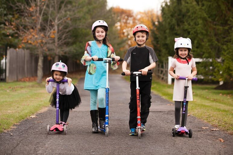 group of young children riding manual kick scooters that are ideal before an electric model