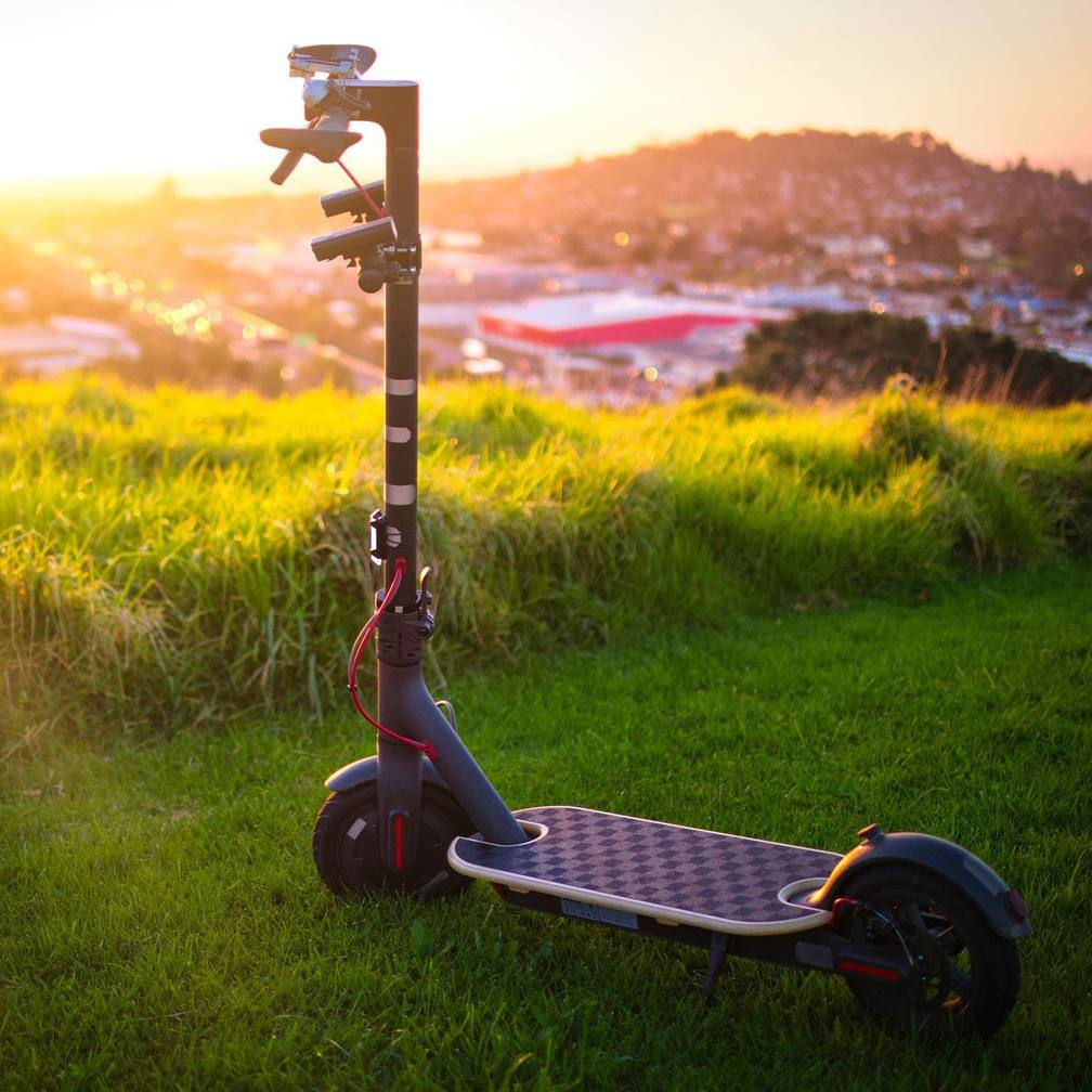 panorama image of the scooter parked on the grass overlooking the city
