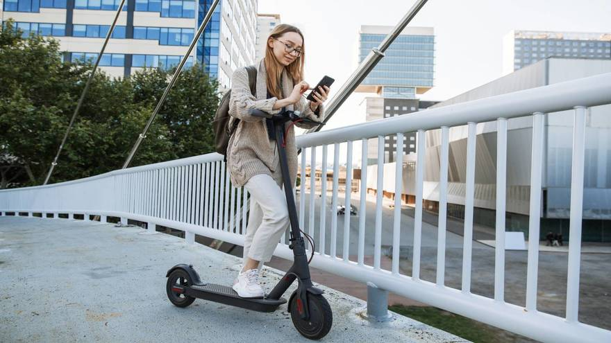 Woman standing with her Xiaomi scooter m365 and using her mobile phone