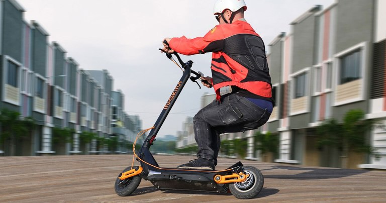 Man riding the Inokim Ox scooter quickly around a right corner