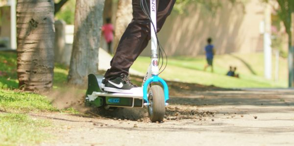 Green Razor E300 electric scooter being ridden on mud and pavement