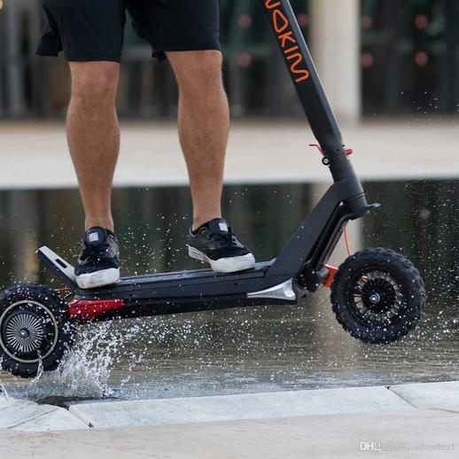 young man in shorts jumping on an Inokim scooter model OX black and orange