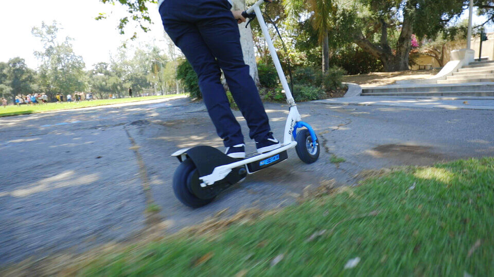 A blue and white e300 E-scooter leaning left for a turn on a park pathway