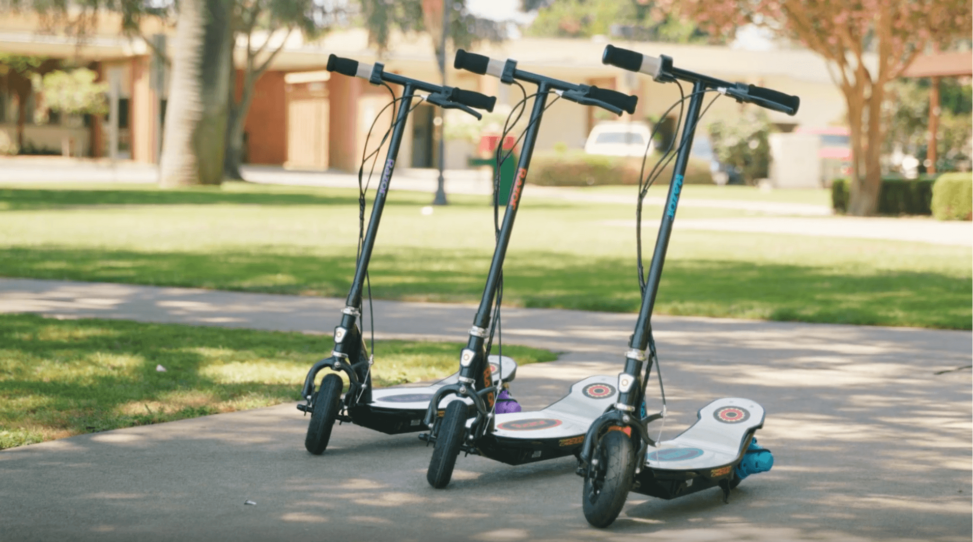 Set of 3 Razor electric scooters resting on stands in blue, orange and pick