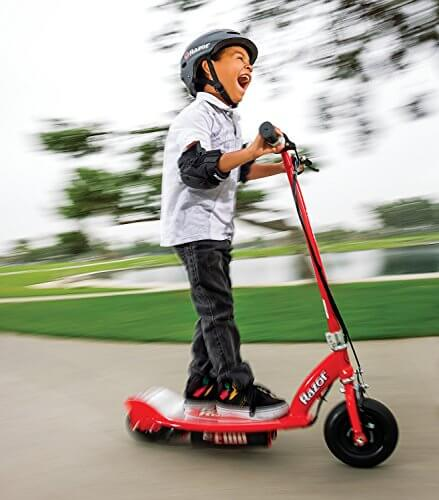8 Year old boy having fun riding a red Razor e100 electric scooter