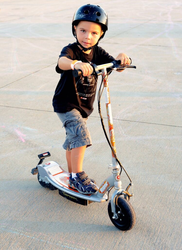 Young boy riding his new escooter.
