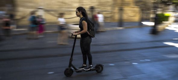 woman riding a pro-scooter in the streets of Seville